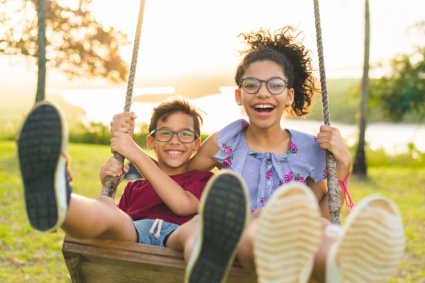 Happy children swinging and smiling at golden sunset Childhood, Swinging, Laughing, Smiling, Fun 12 13 years stock pictures, royalty-free photos & images