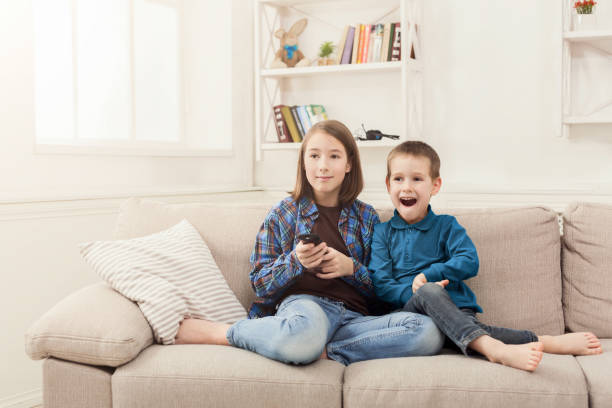 Happy children watching TV at home stock photo