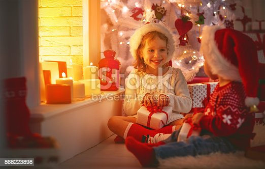 868220646istockphoto happy children with christmas presents near Christmas tree and fireplace 868223898