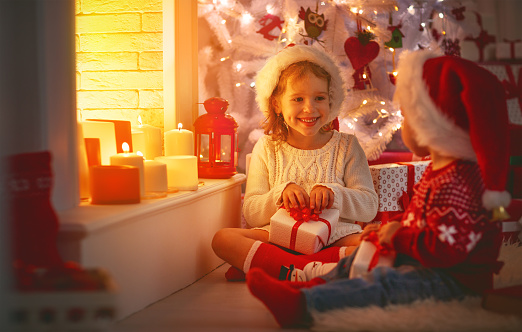 868220646 istock photo happy children with christmas presents near Christmas tree and fireplace 868223898