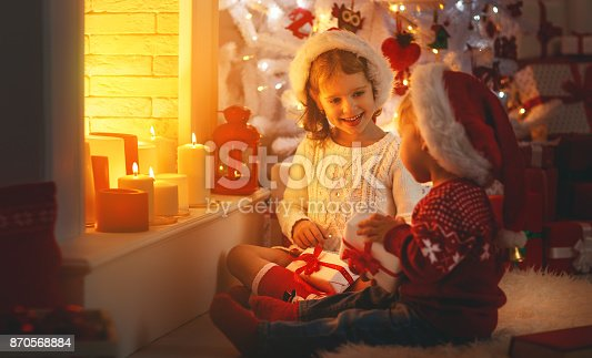 868220646istockphoto happy children with christmas presents near Christmas tree and fireplace 870568884