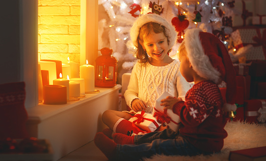 868220646 istock photo happy children with christmas presents near Christmas tree and fireplace 870568884