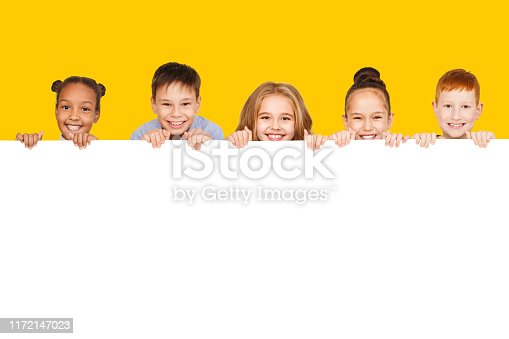 Happy children with empty board for your text isolated over yellow background, copy space