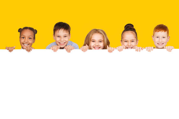 bambini felici con tavola vuota, sfondo giallo - bambino foto e immagini stock