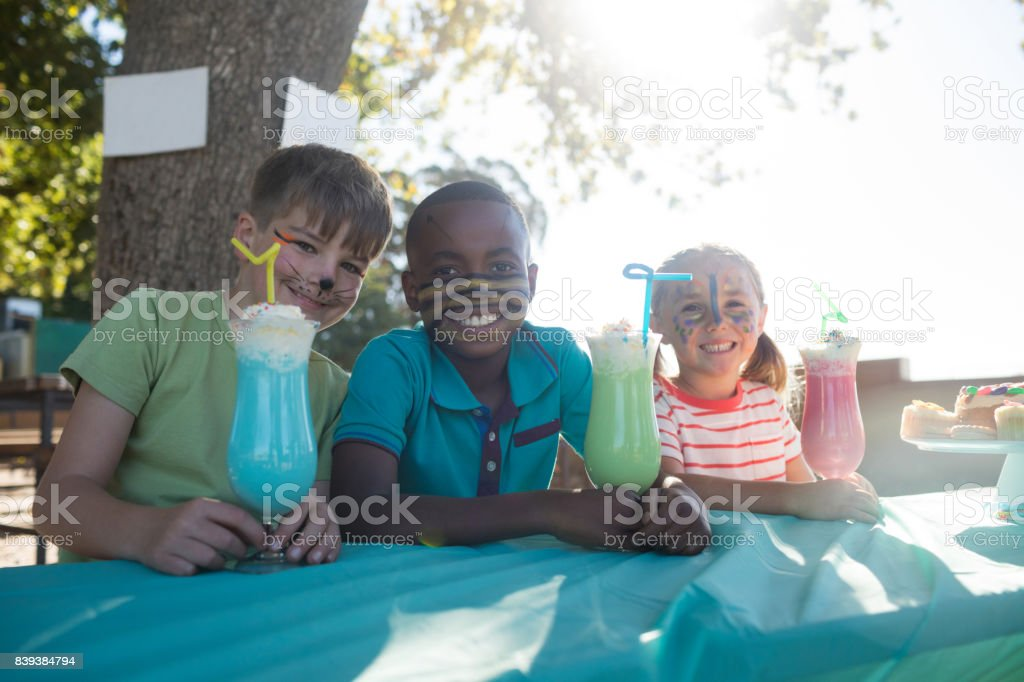 Happy children with face paint having drinks at park stock photo