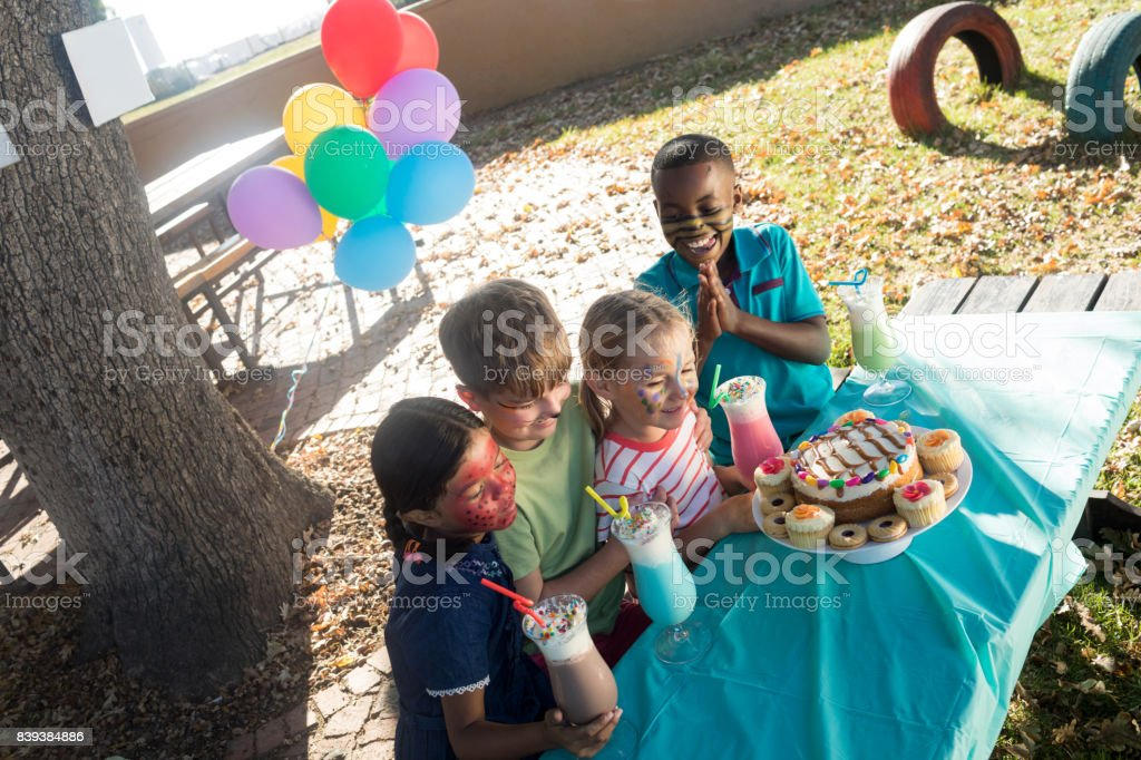 Happy children with face paint having food and drinks at park stock photo