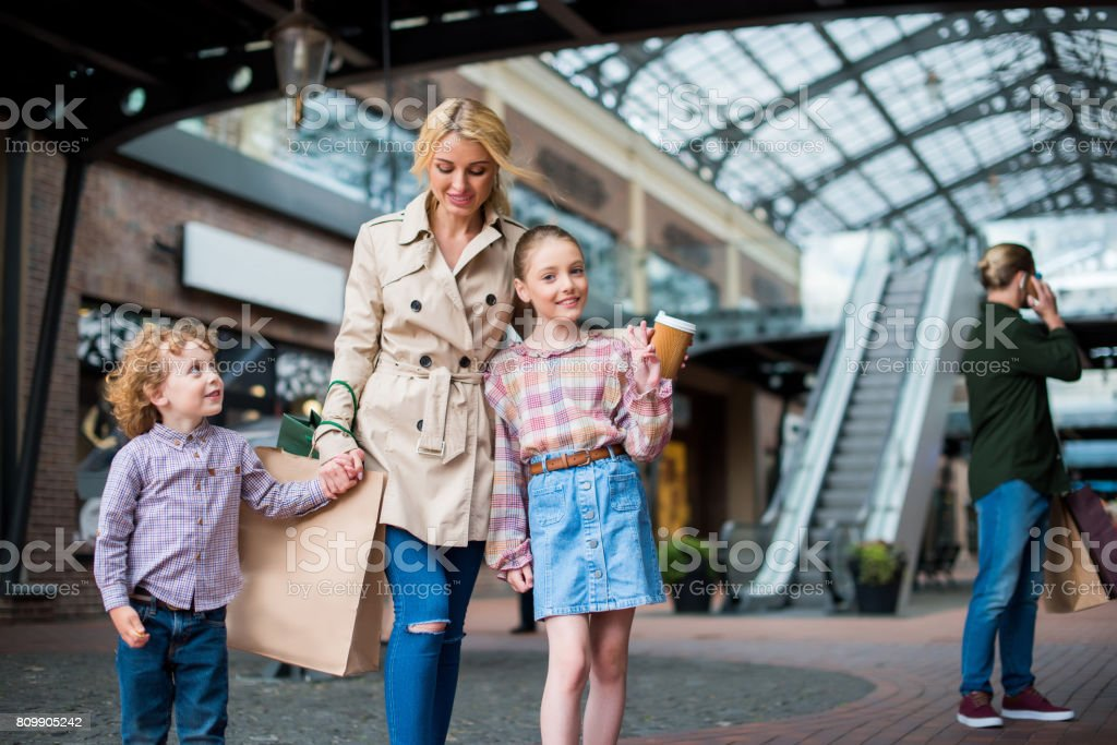 happy children with mother walking with shopping bags at shopping mall stock photo