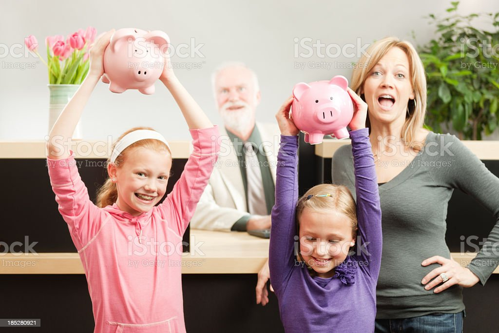 Happy Children with Piggy Banks Savings at Banking Counter Hz royalty-free stock photo