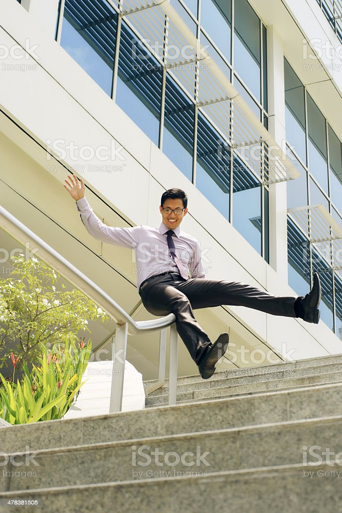 Happy Chinese Businessman Going Downstairs Sliding On Rail stock photo