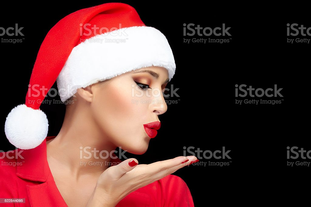 Happy Christmas Girl in Santa Hat Sending a Kiss stock photo