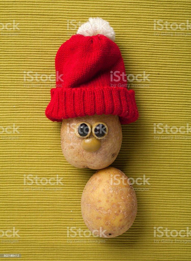 Happy Christmas potato in santa hat on yellow background stock photo