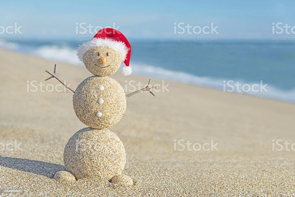 Happy Christmas snowman made from sand wearing santa hat stock photo