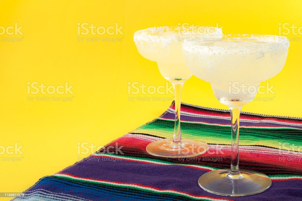 Happy Cinco de Mayo, Mexico fiesta and cocktail party concept theme with two margaritas and a Mexican stripped pattern rug named serape isolated on yellow background with copyspace stock photo