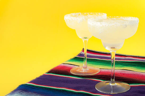 happy cinco de mayo, mexico fiesta and cocktail party concept theme with two margaritas and a mexican stripped pattern rug named serape isolated on yellow background with copyspace - cinco de mayo party stock photos and pictures