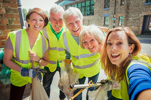 A group of five people taking a selfie. They are wearing high visibility jackets and are participating in a city clean-up.