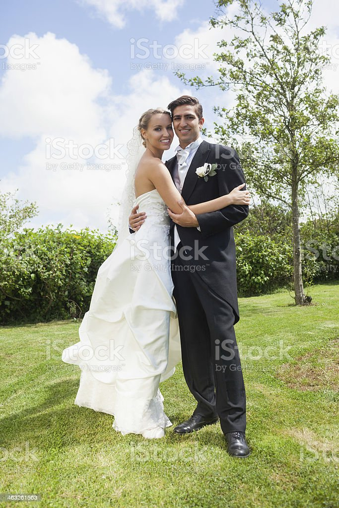Happy classy young newlyweds embracing stock photo