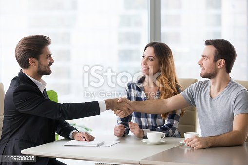 1129638619 istock photo Happy clients couple handshake lawyer thanking for help 1129638635