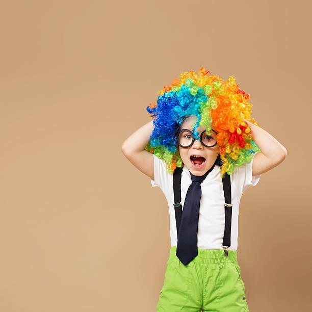 happy clown boy with large colorful wig. - festliche babymode junge stock-fotos und bilder