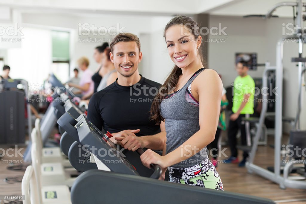 Happy coach assisting young woman in a gym stock photo