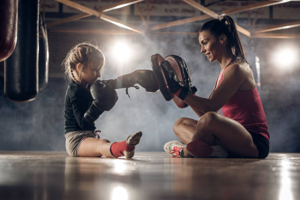 Happy coach exercising boxing punches with little girl on a floor in a health club. stock photo