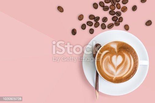 A cup of Latte coffee with scattered roasted coffee beans on pastel millennial pink tone background.  Happy coffee Latte