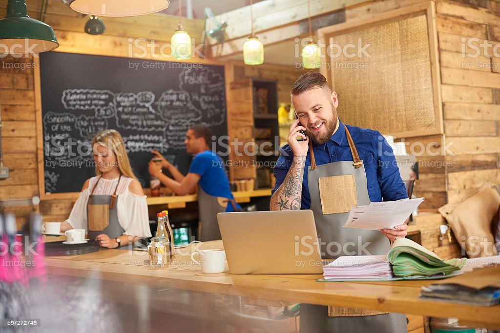 Happy Coffee shop owner on the phone royalty-free stock photo