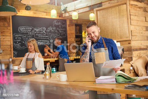 istock Happy Coffee shop owner on the phone 597272748