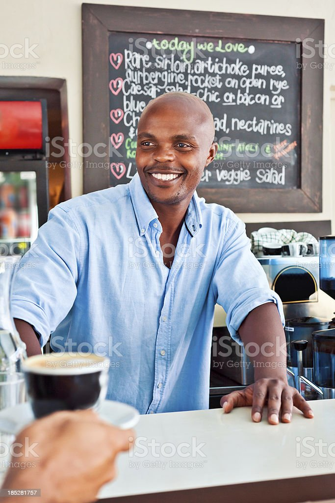 Happy Coffee Shop Owner Friendly african man standing behind the bar counter and serving coffee in coffee shop. Adult Stock Photo