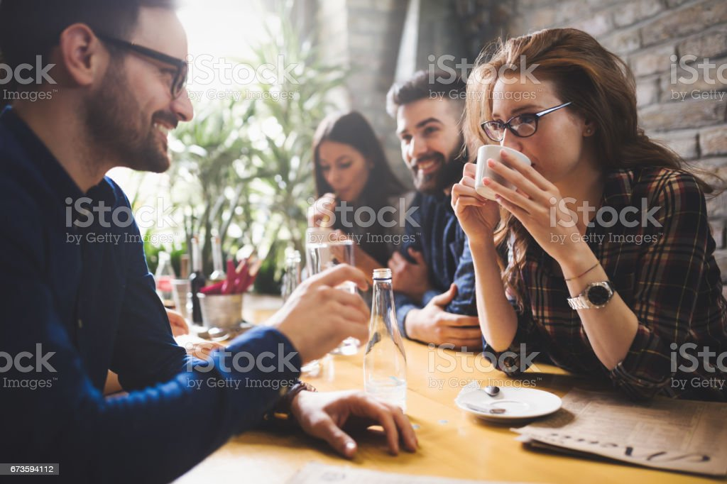 Happy colleagues from work socializing in restaurant and eating together stock photo