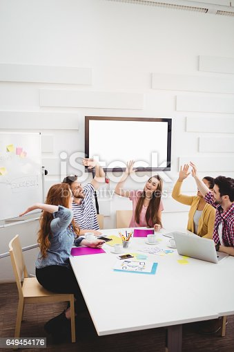 649403294 istock photo Happy colleagues giving high-fives in meeting at creative office 649454176