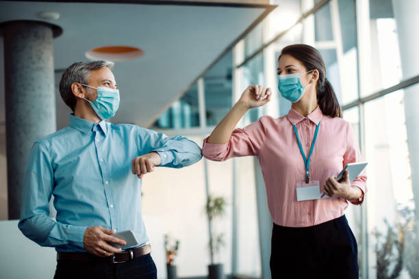 Happy colleagues greeting with elbows in a hallway during coronavirus pandemic. stock photo