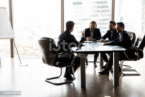 843963182 istock photo Happy colleagues having fun at meeting in boardroom 1249232579