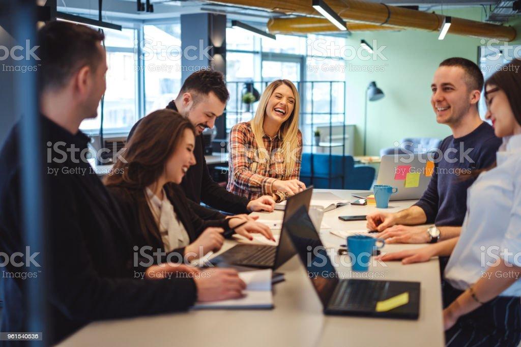 Heureux collègues riant dans la réunion de bureau photo libre de droits