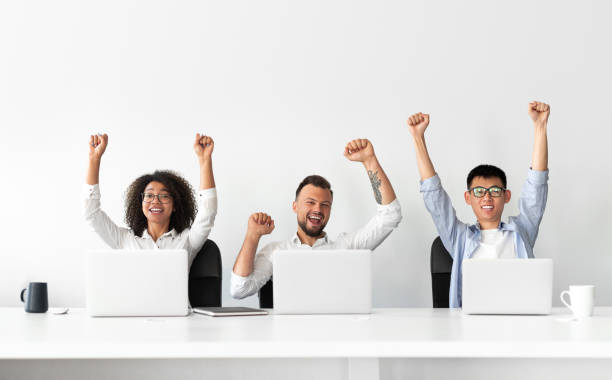 Happy colleagues sitting at laptops and celebrating success stock photo