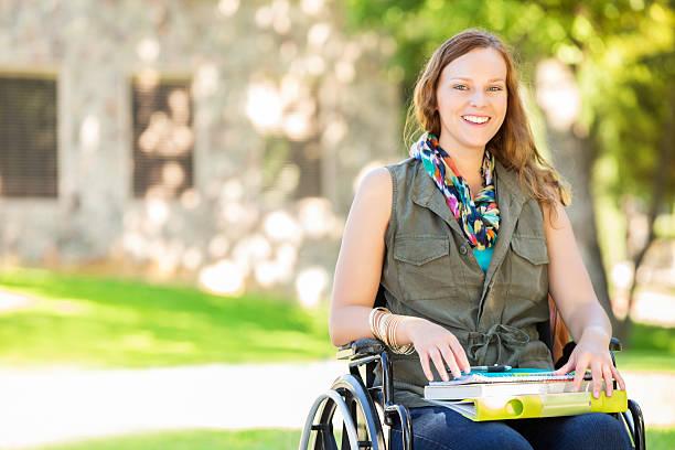 happy college girl in wheelchair on campus - sedia a rotelle foto e immagini stock