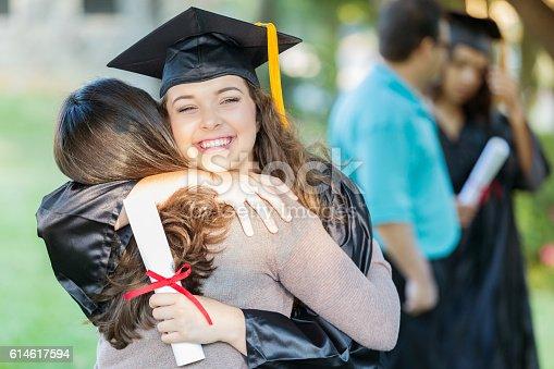 istock Happy college grad hugs her mom 614617594