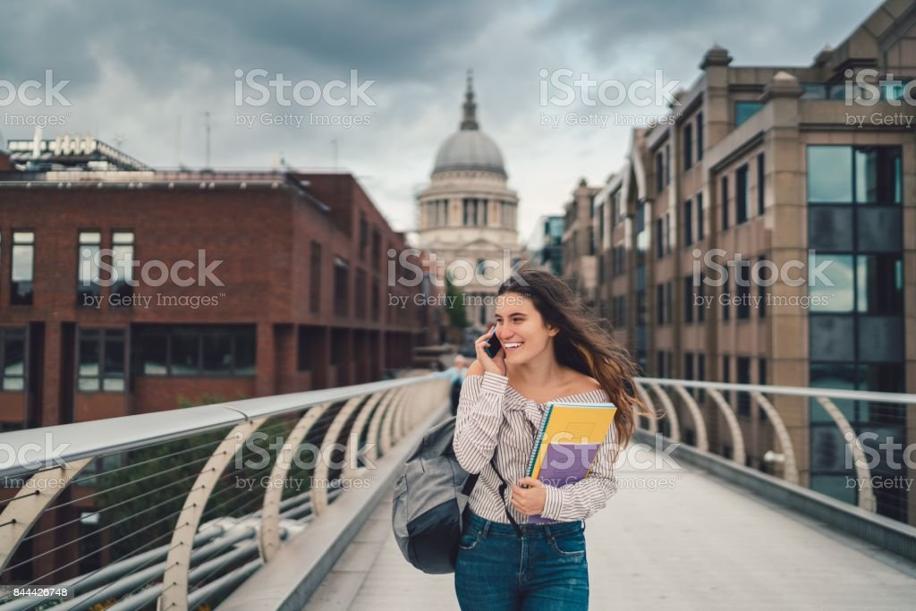 Happy college student in London using phone royalty-free stock photo