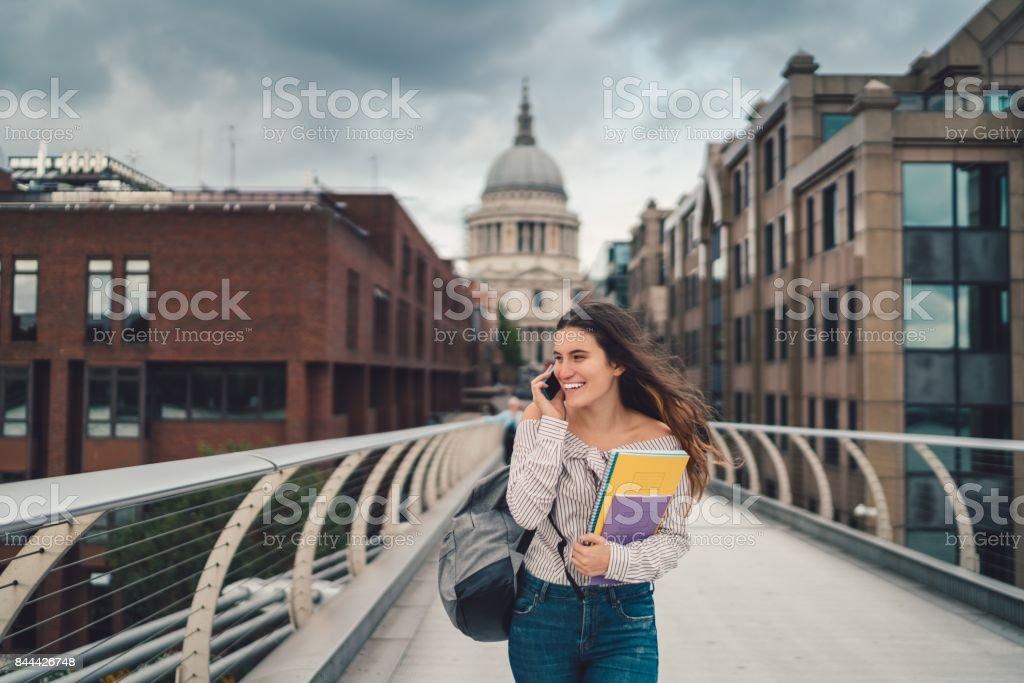 Glücklich College-Studentin in London mit Telefon Lizenzfreies stock-foto