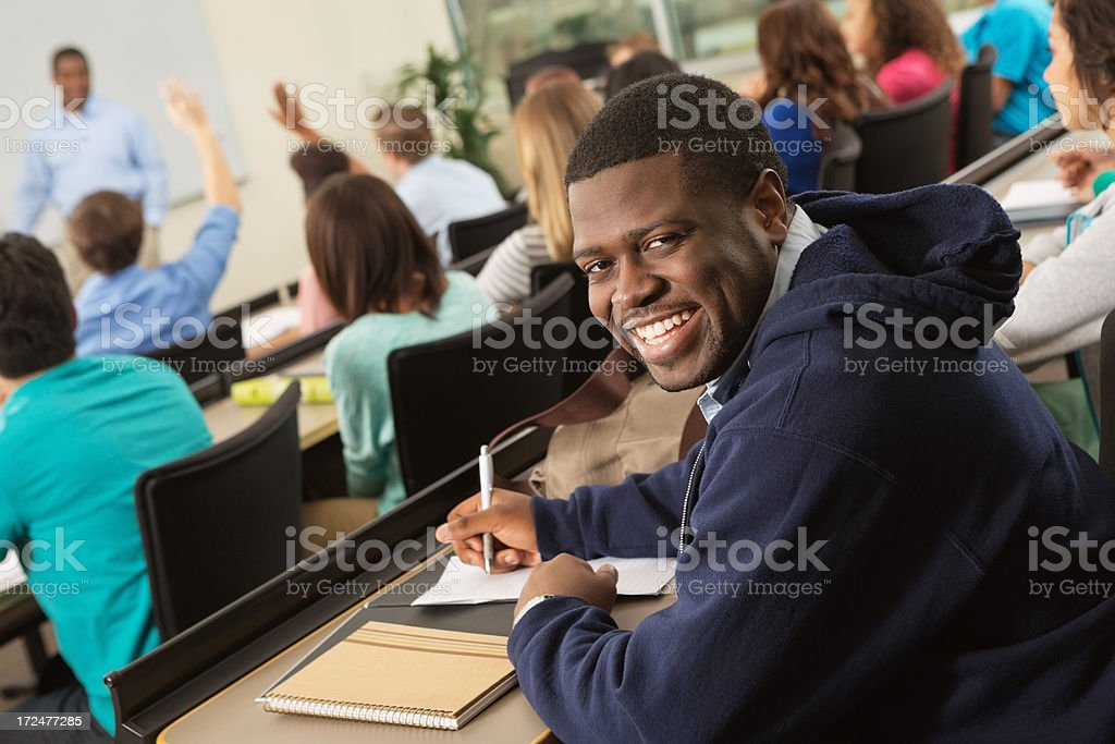 Happy college student taking notes during lecture in classroom royalty-free stock photo