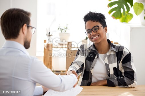 istock Happy confident african applicant shaking hand of hr getting hired 1127950017