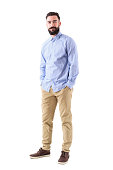 istock Happy confident bearded business man in formal wear with hands in pockets looking at camera 908611616