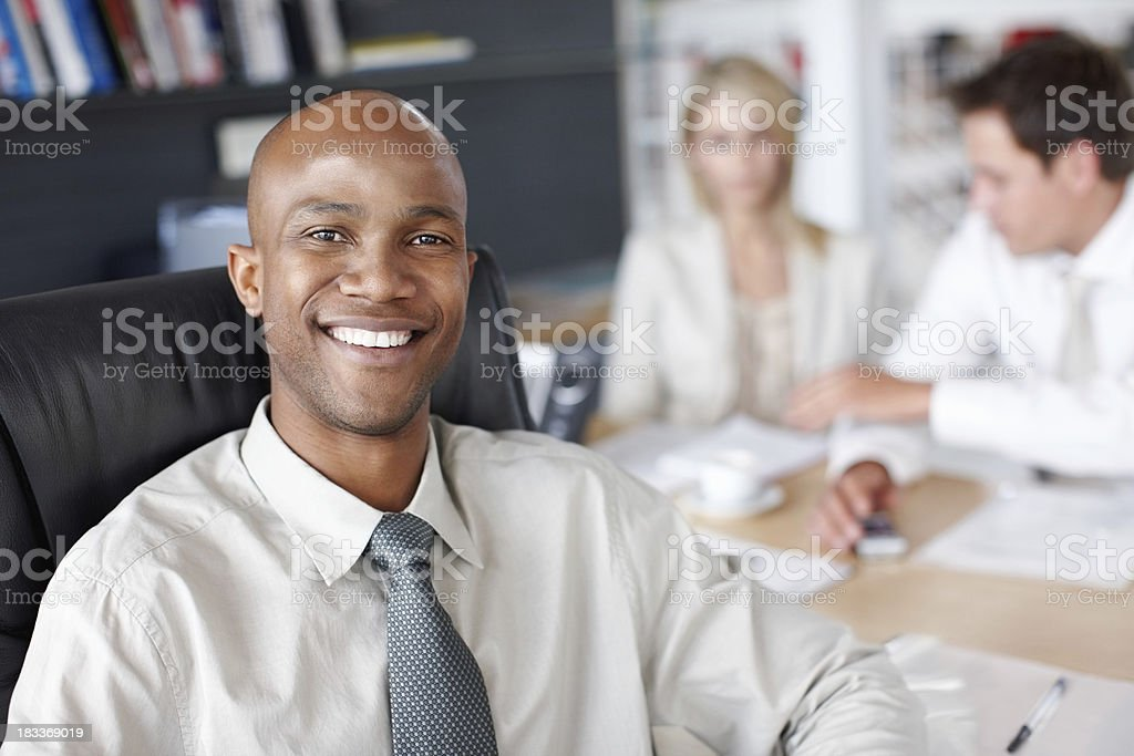Happy confident business man with coworkers in background stock photo