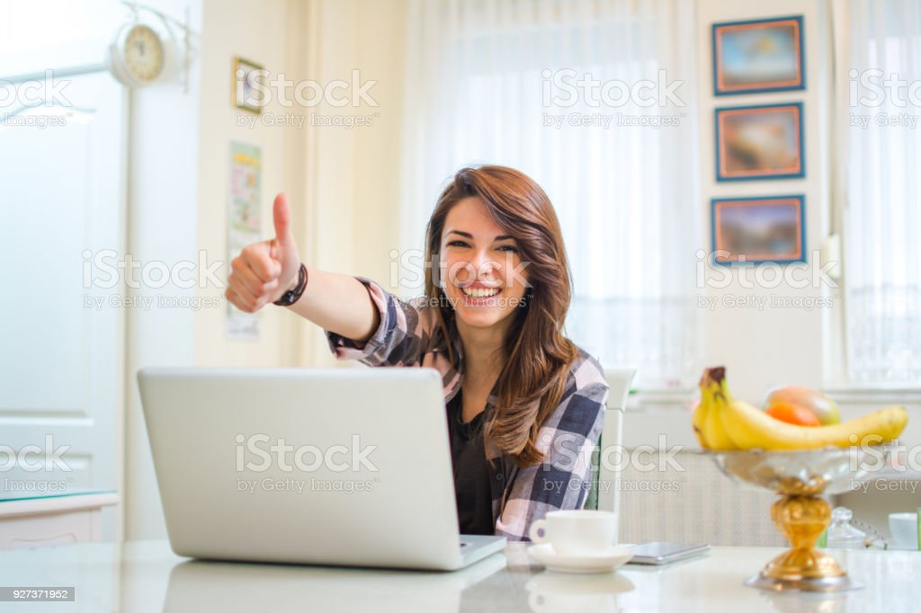 Happy confident entrepreneur working with a laptop gesturing thumbs up looking at camera. stock photo