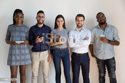 Happy confident successful multiethnic workers standing near wall portrait. Smiling mixed race group of young employees looking at camera, international company staff, hr managers, dream team concept.