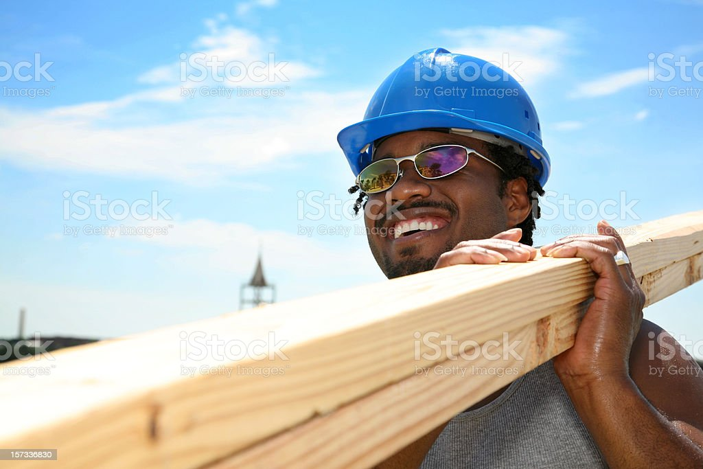 Happy Construction Worker, African American, carrying wood royalty-free stock photo