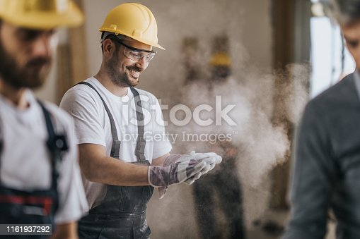 Young happy manual worker cleaning sawdust from his protective gloves at construction site.