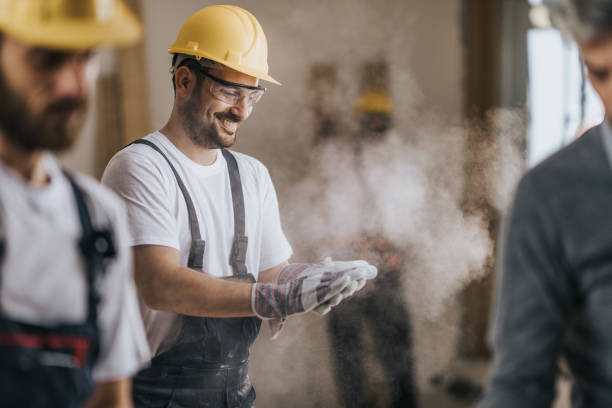 Happy construction worker cleaning his gloves from sawdust at in renovating apartment. stock photo