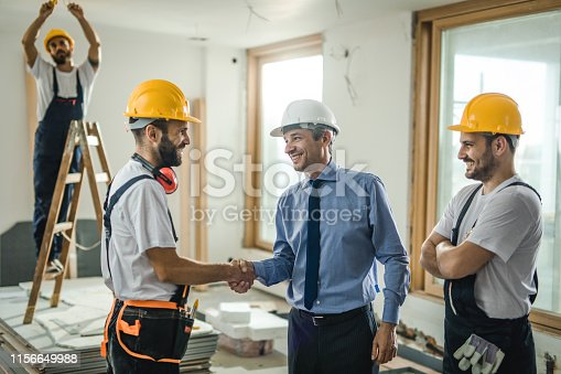 961745166istockphoto Happy construction worker greeting a building contractor at renovating apartment. 1156649988