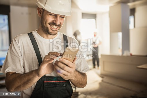 Happy male worker text messaging on smart phone while being in renovating home.