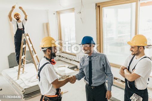 961745166istockphoto Happy construction workers came to an agreement with an architect during home renovation process. 1129346430